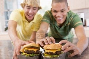 two hungry boys reaching for massive hamburgers as their own version of the hunger games